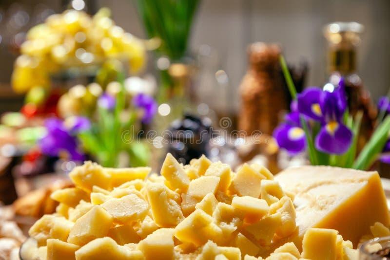Primer de la placa con los pedazos de parmesano italiano en el banquete en la tabla entre diversos platos Cumpleaños del concepto fotos de archivo