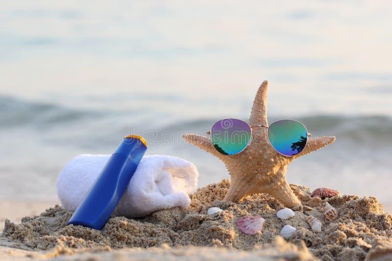 Primer de la playa del verano con las gafas de sol en la crema de la protección de las estrellas de mar y del sol, toalla en play fotografía de archivo libre de regalías
