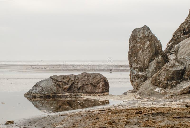 Primer de la roca gigante que miente en agua cerca de la playa con las rocas dentadas en el acantilado próximo con la espuma y ru fotos de archivo