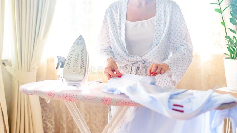 Primer de la ropa que plancha de la mujer en el tablero que plancha foto de archivo libre de regalías