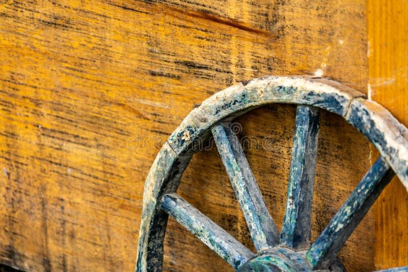 Primer de la rueda de carro resistida edad con los rayos de madera que se inclinan contra una caja de madera amarilla imagen de archivo