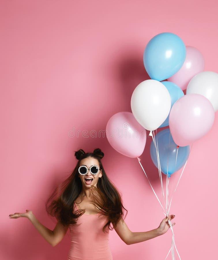 Primer de la situación rubia linda de la muchacha en un estudio, sonriendo extensamente y jugando con los baloons azules y rosado imagenes de archivo