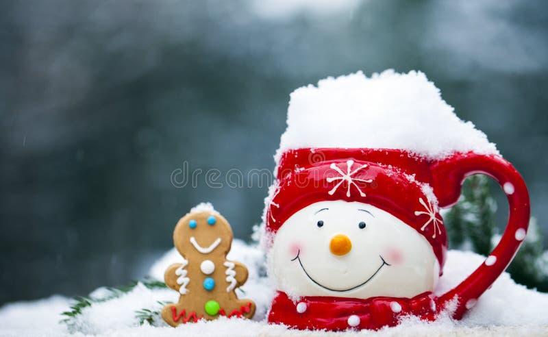 Primer de la taza con la cara del muñeco de nieve por completo de la nieve y del pan de jengibre imagen de archivo