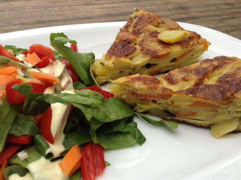 Primer de la tortilla española con la ensalada fotos de archivo