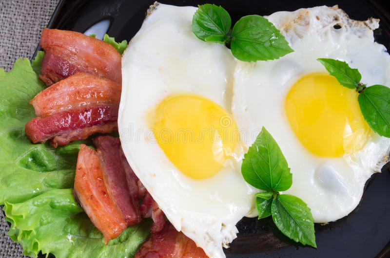 Primer de la visión superior en una placa con los huevos fritos y el tocino frito imagen de archivo libre de regalías