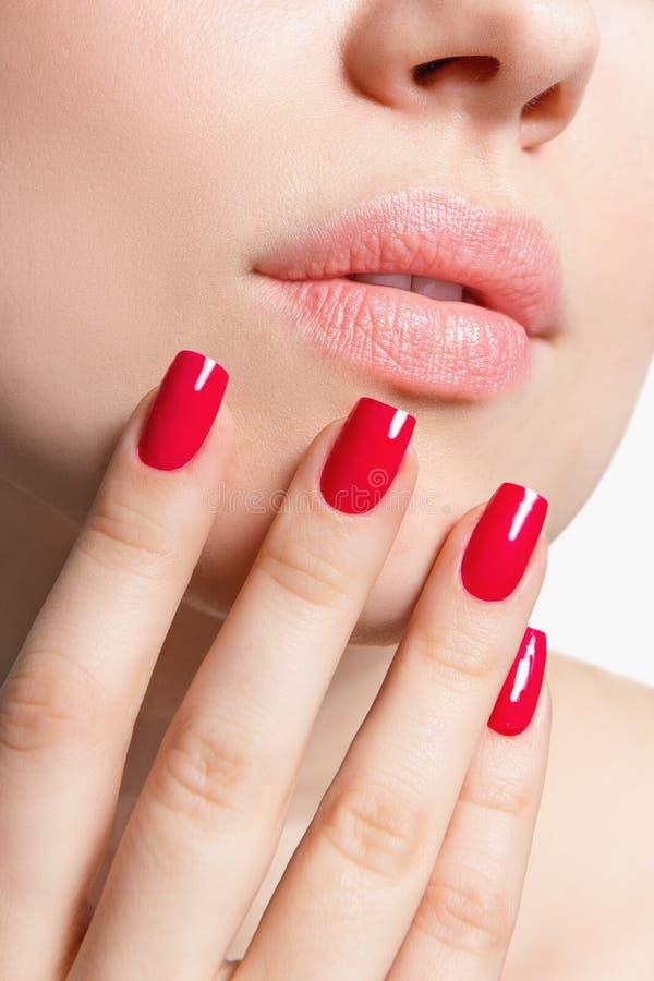 Primer de labios y de la mano femeninos con el esmalte de uñas rojo fotografía de archivo libre de regalías
