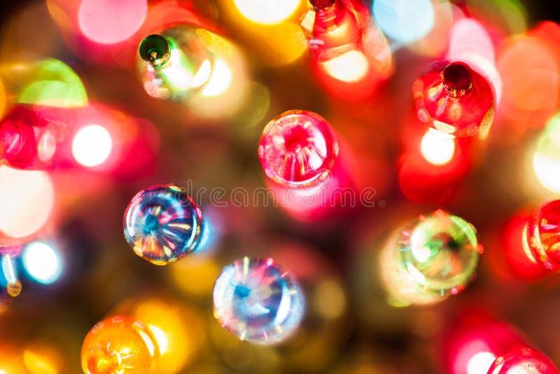Primer de las bombillas del árbol de navidad en el bokeh colorido imágenes de archivo libres de regalías