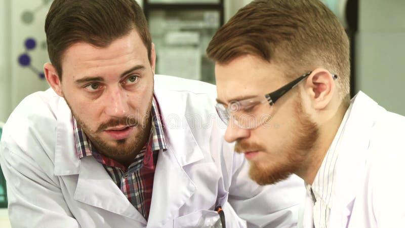 Primer de las caras de los técnicos de laboratorio que conducen una conversación seria fotografía de archivo