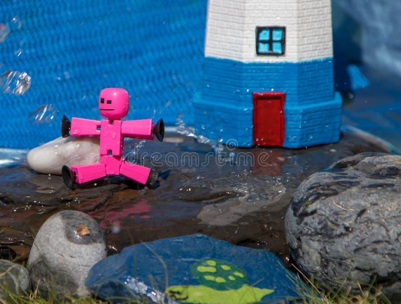 Primer de las figuras del palillo del juguete que juegan en rocas mojadas imagen de archivo