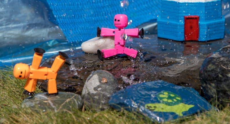 Primer de las figuras del palillo del juguete que juegan en rocas mojadas en sol del verano imagen de archivo