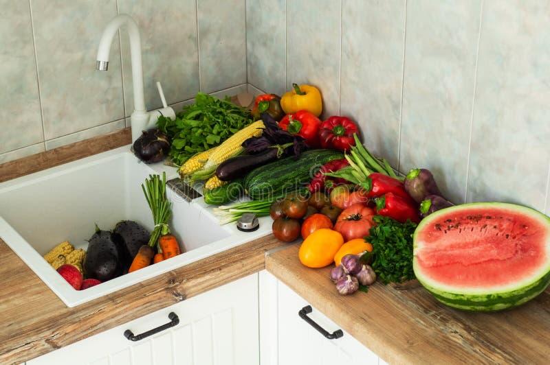 Primer de las frutas y verduras que se lava Verduras frescas que salpican en agua antes de cocinar imagen de archivo