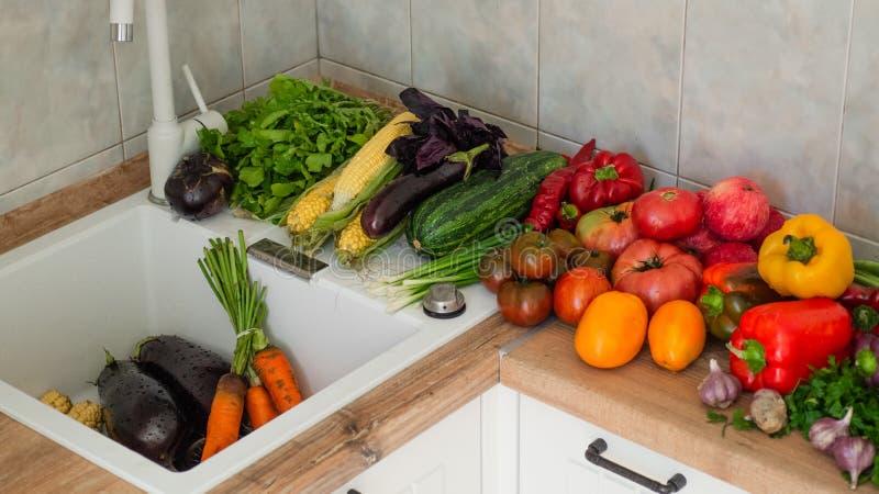 Primer de las frutas y verduras que se lava Verduras frescas que salpican en agua antes de cocinar fotos de archivo