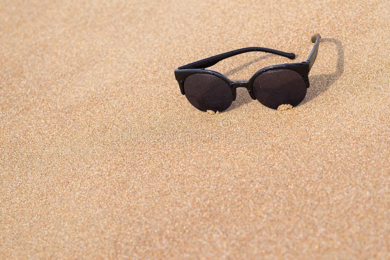 Primer de las gafas de sol en la costa arenosa fotos de archivo libres de regalías