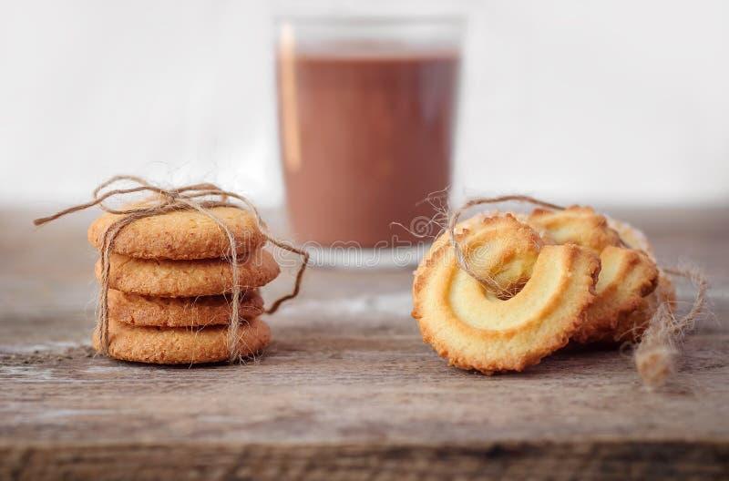 Primer de las galletas de mantequilla en fondo de madera rústico con una taza fotografía de archivo