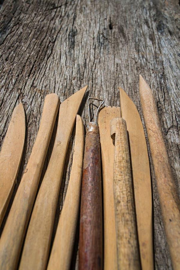 Primer de las herramientas de la cerámica en el fondo de madera imagenes de archivo