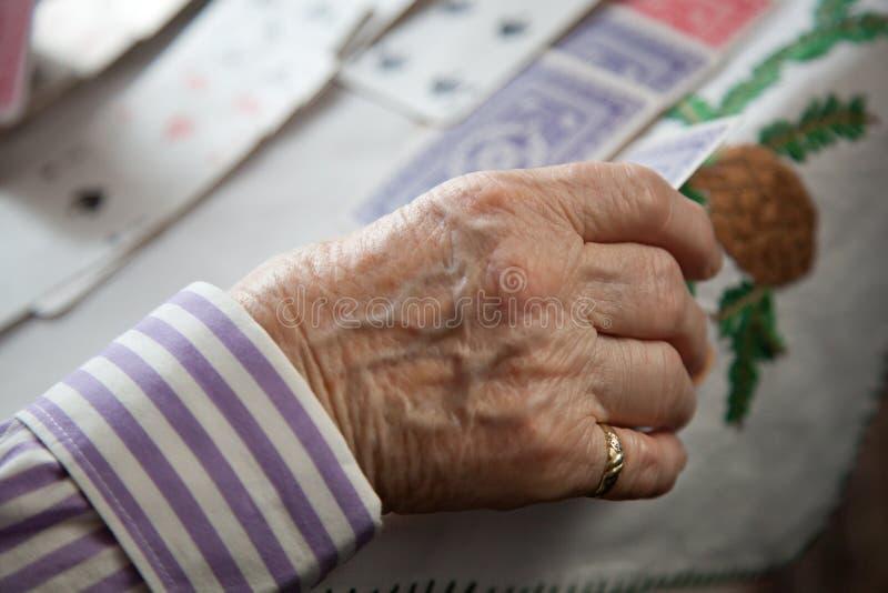 Primer de las manos arrugadas de la se?ora mayor que juegan el solitario fotografía de archivo