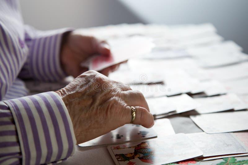 Primer de las manos arrugadas de la se?ora mayor que juegan el solitario fotos de archivo libres de regalías