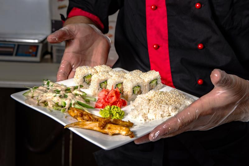 Primer de las manos del cocinero que ruedan encima del ajuste del sushi en la placa en cocina fotografía de archivo libre de regalías
