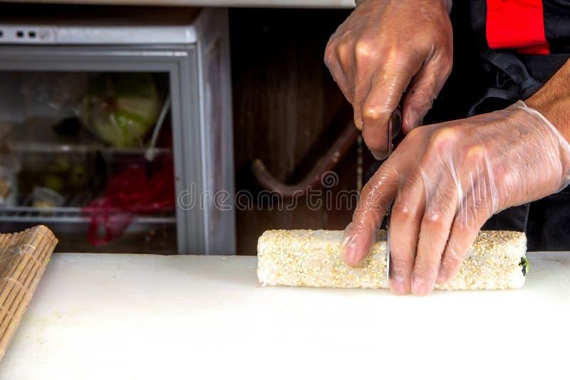 Primer de las manos del cocinero que ruedan encima de cortes del sushi en porciones en cocina fotografía de archivo libre de regalías
