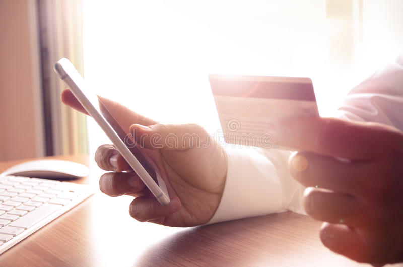 Primer de las manos del hombre que sostienen tarjetas de crédito y que usan el teléfono móvil fotos de archivo libres de regalías
