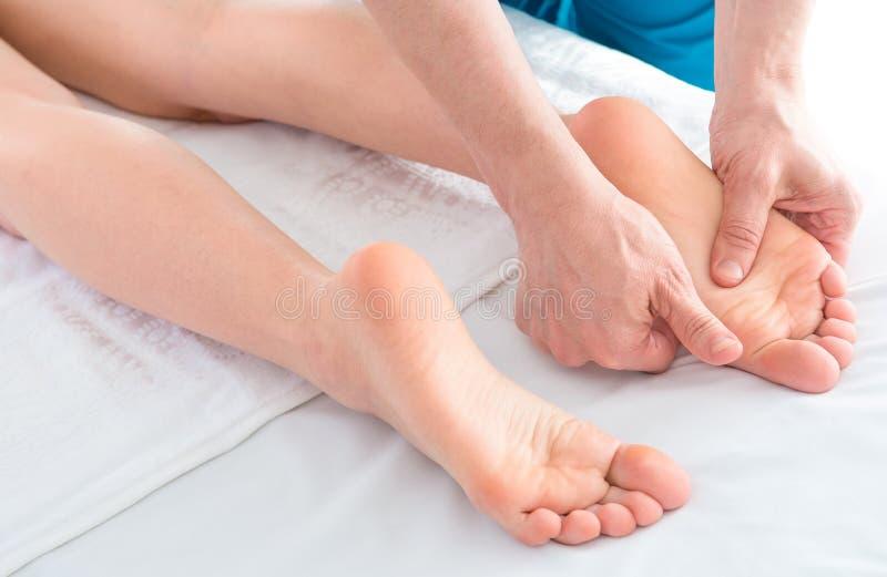 Primer de las manos del masajista que hacen el masaje de la pierna de la mujer imagen de archivo