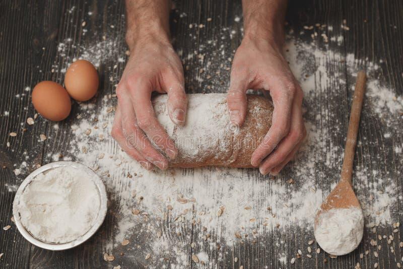 Primer de las manos del panadero del ` s de los hombres en el pan negro con el polvo de la harina Hornada y concepto de la pastel foto de archivo libre de regalías