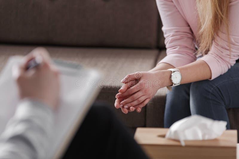 Primer de las manos del ` s de la mujer durante el asesoramiento de la reunión con un profe imagen de archivo libre de regalías