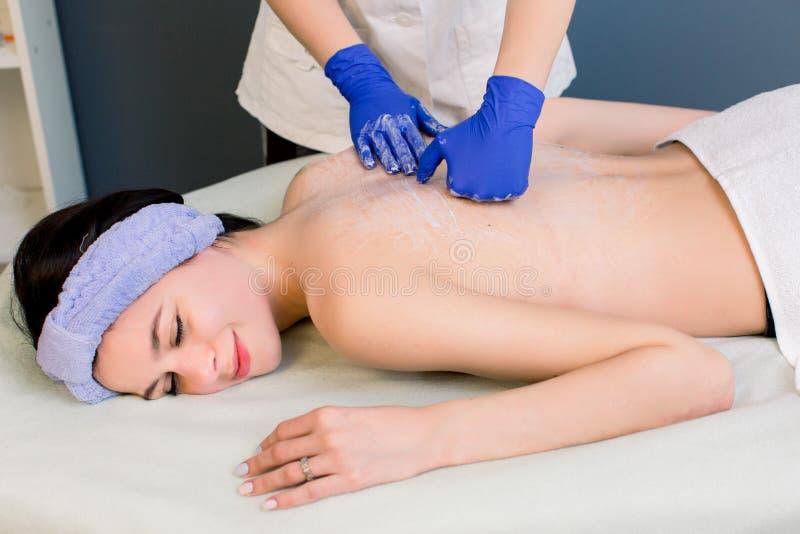 Primer de las manos femeninas del masajista en los guantes de goma azules que dan detrás masaje a una mujer bonita joven en balne imágenes de archivo libres de regalías