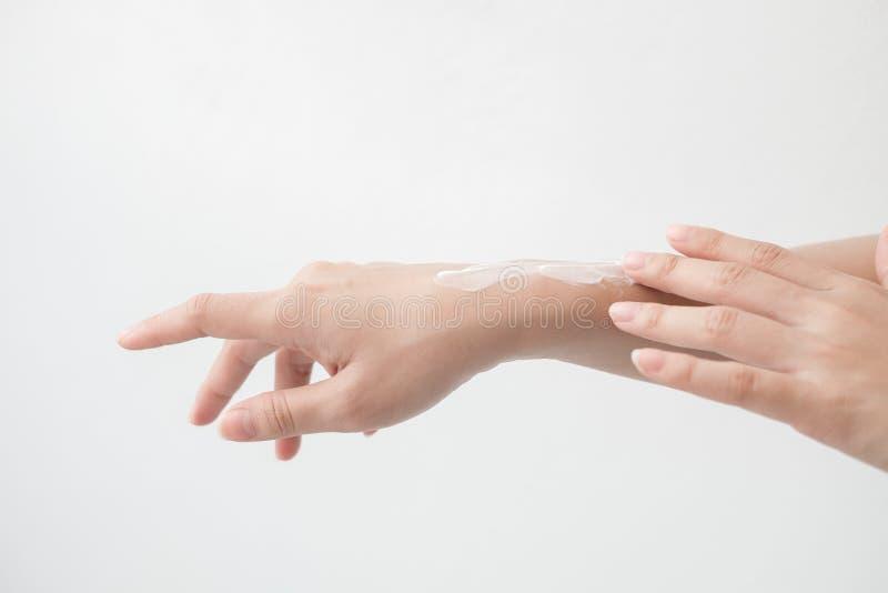 Primer de las manos femeninas hermosas que llevan a cabo las manos y que aplican una crema hidratante La mano de la mujer de la b fotografía de archivo libre de regalías