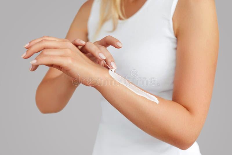 Primer de las manos femeninas que aplican la crema de la mano Cuidado de piel de la mano Las mujeres utilizan la loción del cuerp fotos de archivo