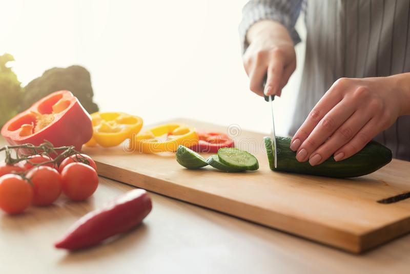 Primer de las manos femeninas que cocinan la ensalada de las verduras en cocina fotos de archivo libres de regalías