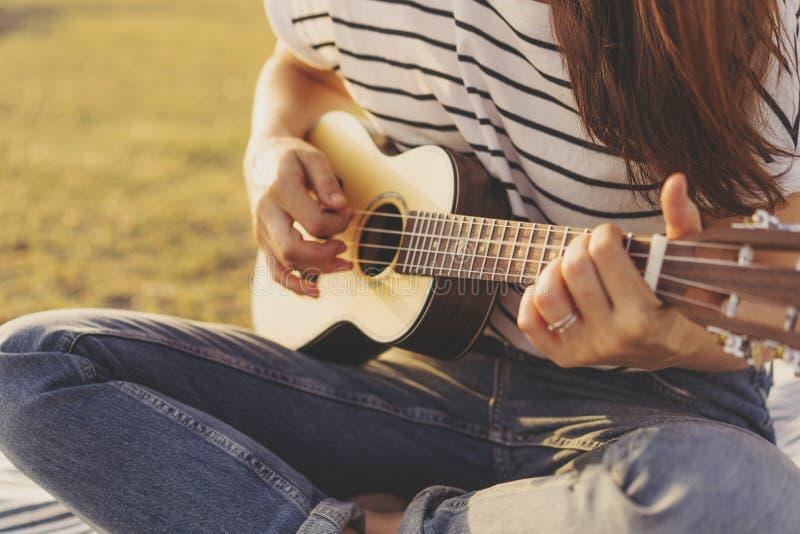 Primer de las manos femeninas que tocan la guitarra del ukelele imagenes de archivo