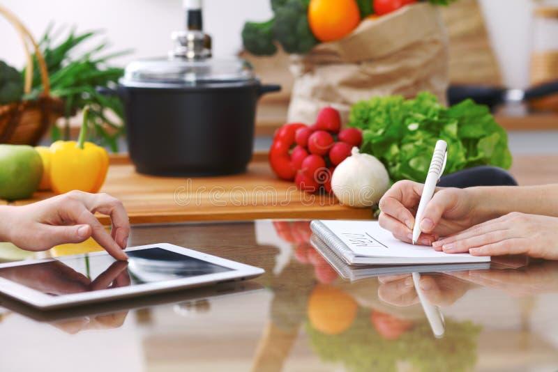 Primer de las manos humanas que cocinan en cocina usando la almohadilla táctil Las mujeres discuten un menú Comida sana, comida v imagen de archivo