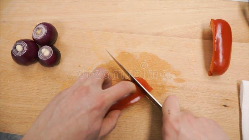 Primer de las manos humanas que cocinan la ensalada de las verduras en cocina en la tabla clip Concepto sano de la comida y del v foto de archivo libre de regalías
