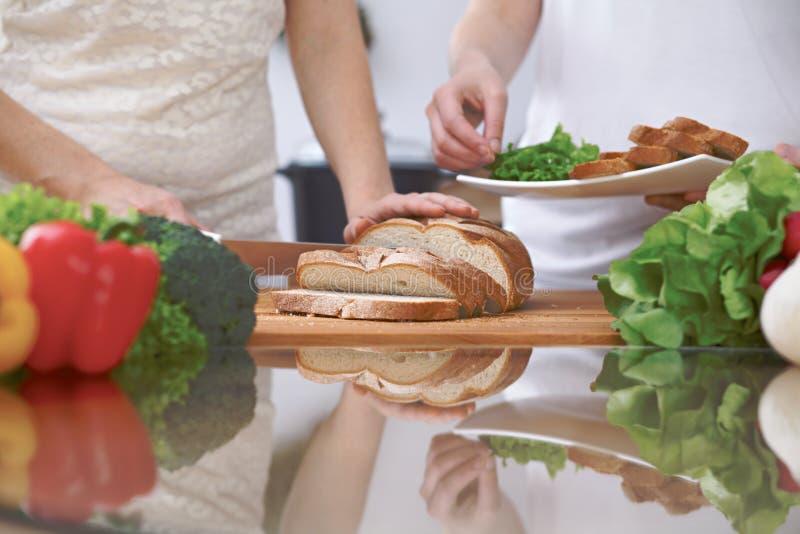 Primer de las manos humanas que cortan el pan en una cocina Amigos que se divierten mientras que prepara la ensalada fresca El co imagen de archivo