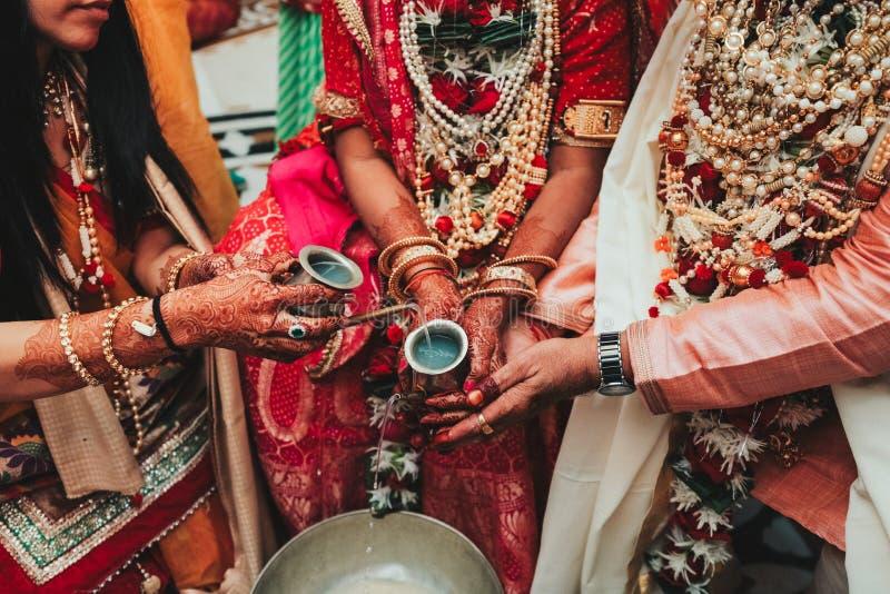 Primer de las manos indias del ` s de la novia cubiertas con el mehndi que lleva a cabo la explosión fotos de archivo