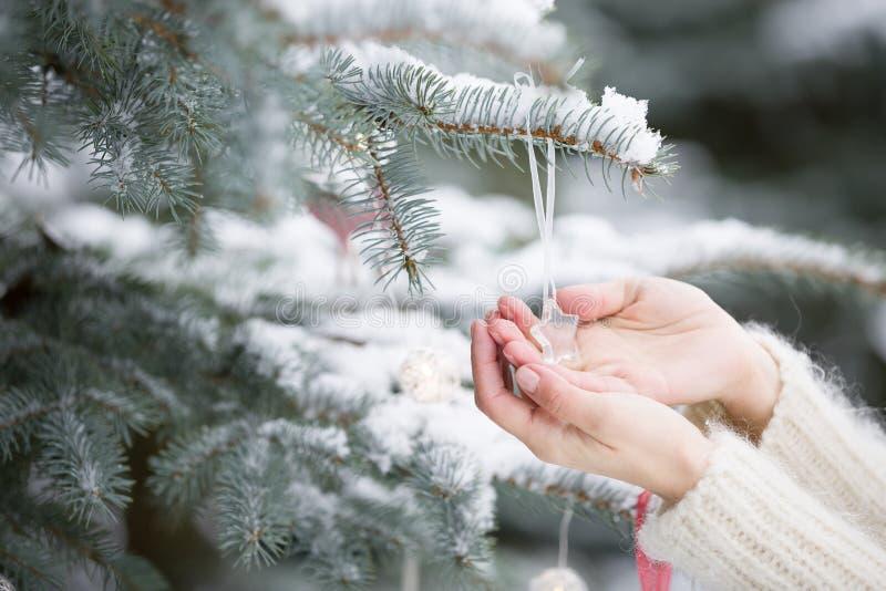Primer de las manos de la mujer que adornan el árbol de navidad con la decoración cristalina de la estrella al aire libre Celebra foto de archivo
