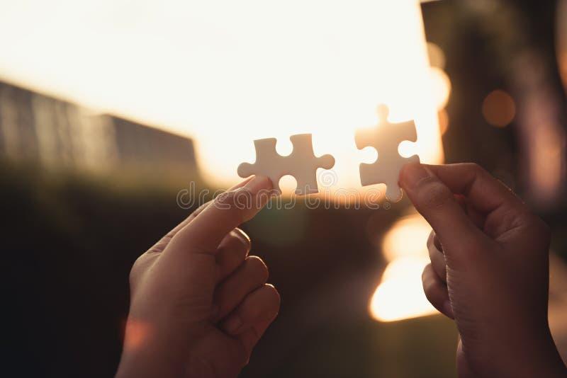 Primer de las manos de la mujer que se unen a pedazos de rompecabezas juntos , Soluciones del negocio fotografía de archivo