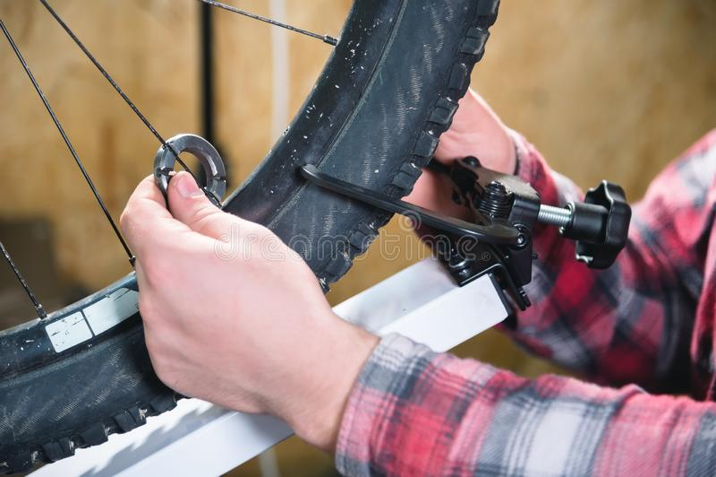 Primer de las manos de los hombres con una llave especializada en un soporte en el taller que aprieta los rayos de la rueda imagen de archivo libre de regalías