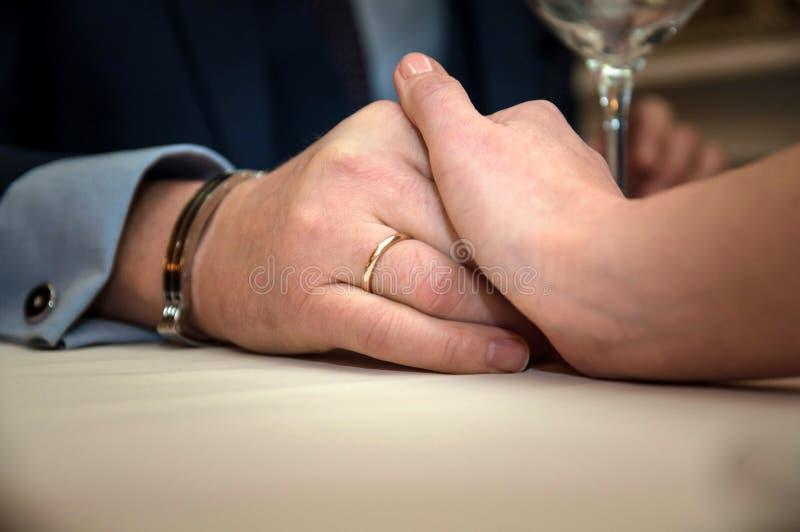 Primer de las manos de los pares en la tabla del restaurante con los vidrios de champ?n Cena rom?ntica de los pares en un restaur fotos de archivo
