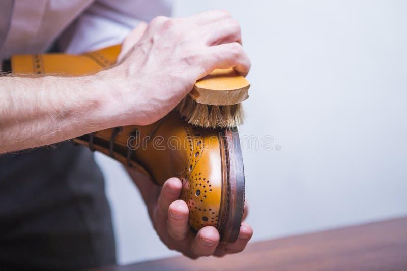 Primer de las manos masculinas con el cepillo de pulido para Tan Brogue Derby Boots fotografía de archivo libre de regalías
