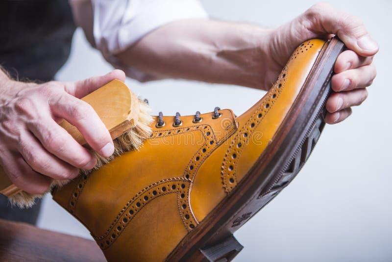 Primer de las manos masculinas con el cepillo de pulido para Tan Brogue Derby Boots foto de archivo libre de regalías