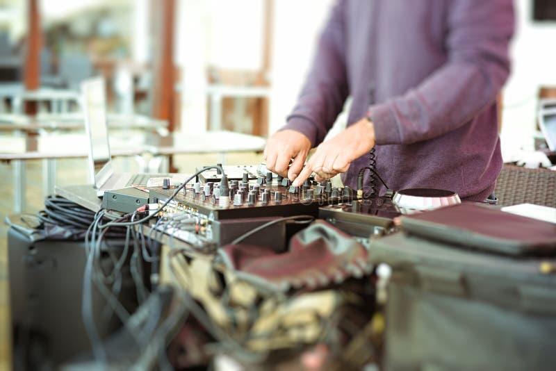 Primer de las manos masculinas que mezclan audio con imágenes de archivo libres de regalías