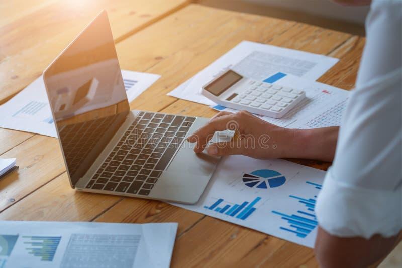 Primer de las manos masculinas usando el ordenador portátil, las manos que mecanografían en el teclado del ordenador portátil, vi foto de archivo libre de regalías