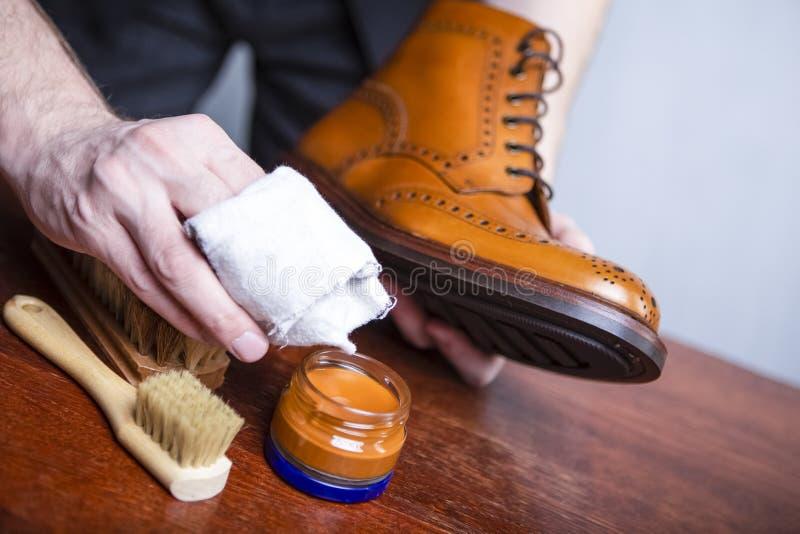 Primer de las manos para hombre que pulen a Derby Brogue Boots bronceado de cuero usar la variedad de cepillos y polaco de la cer fotografía de archivo