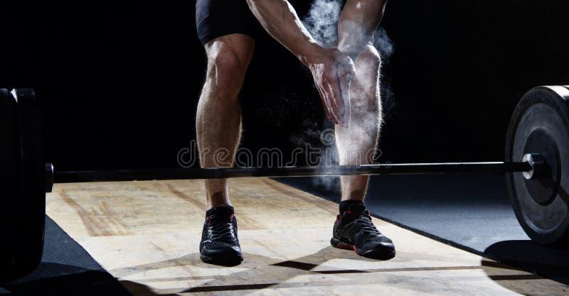 Primer de las manos que aplauden del weightlifter antes del entrenamiento del barbell en imágenes de archivo libres de regalías