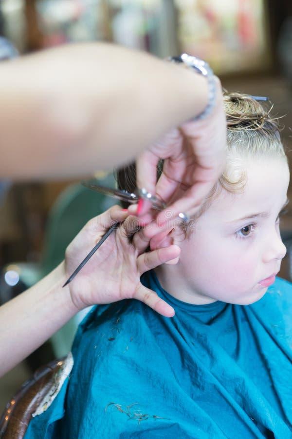 Primer de las manos que cortan el pelo del muchacho imagenes de archivo