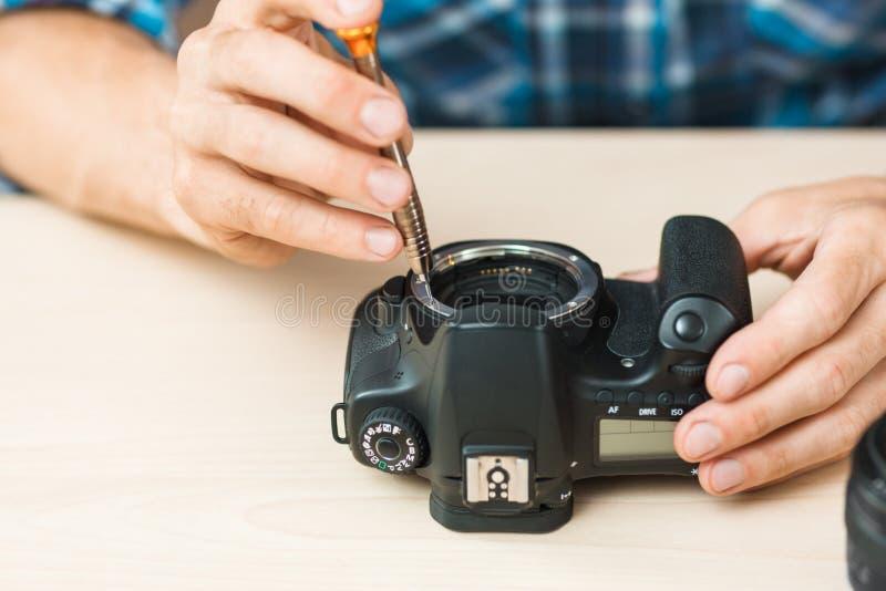 Primer de las manos que desmontan la cámara de la foto imagen de archivo