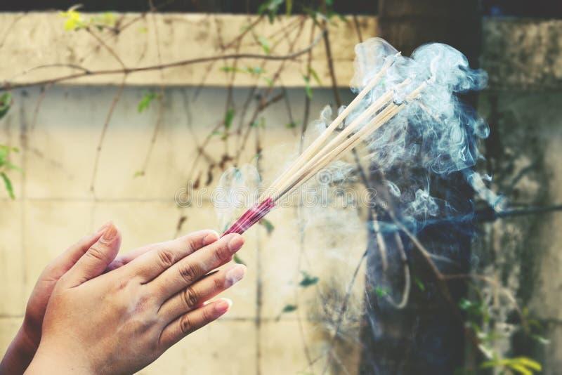 Primer de las manos que sostienen los palillos ardientes del incienso que fuman foto de archivo