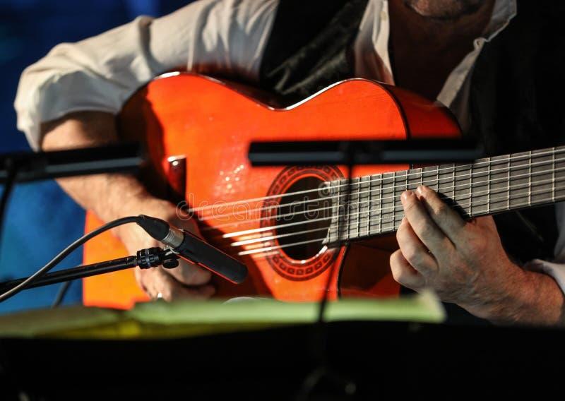 Primer de las manos de un hombre que tocan la guitarra clásica foto de archivo libre de regalías
